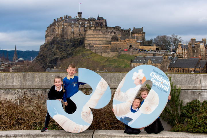 Three children holding a large number 30 with Edinburgh Castle in the background